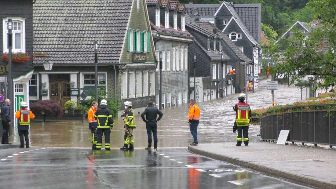 Einsatzkräfte stehen an einer überschwemmten Straße