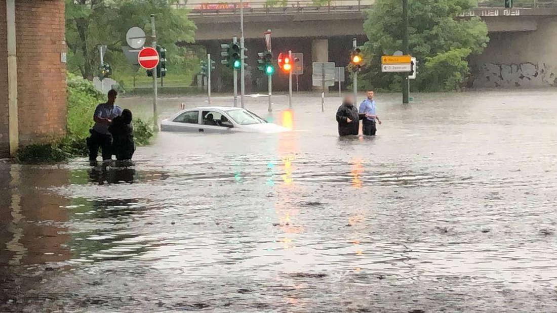Zwei Polizisten mit zwei Menschen im Hochwasser in Düsseldorf.