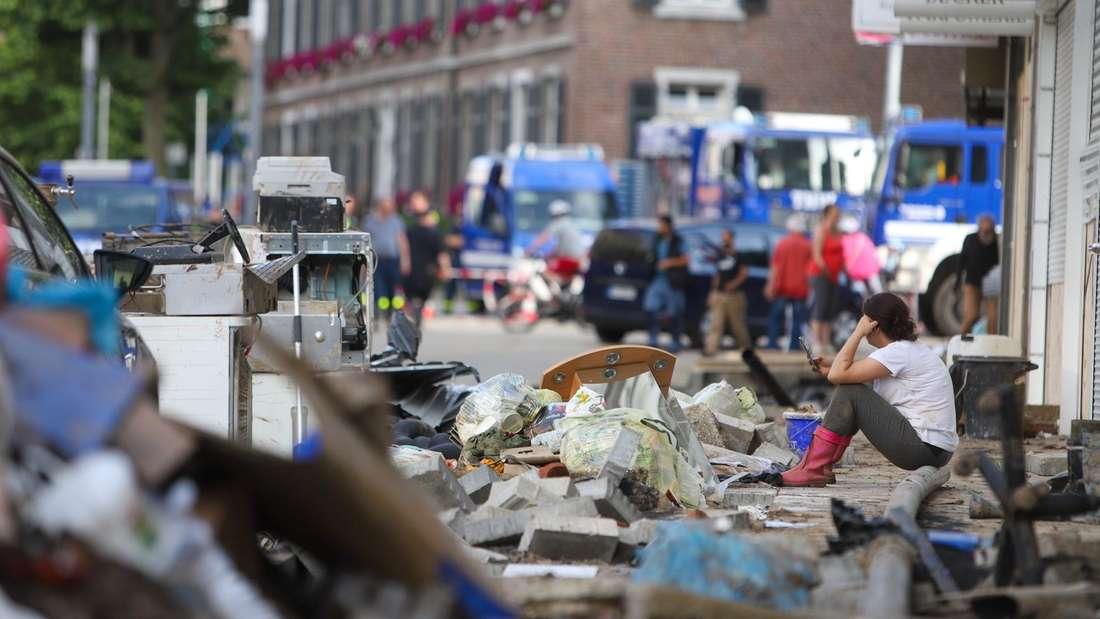 Ein Anwohnerin sitzt auf Trümmern des Unwetters vor einem Haus in Stolberg.