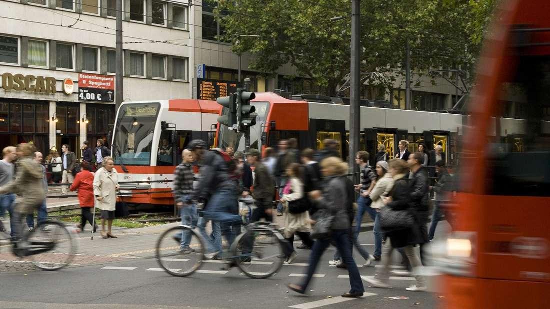 """Die Umstiegshaltestelle """"Zülpicher Platz"""" mit Personen vor der KVB-Bahn."""