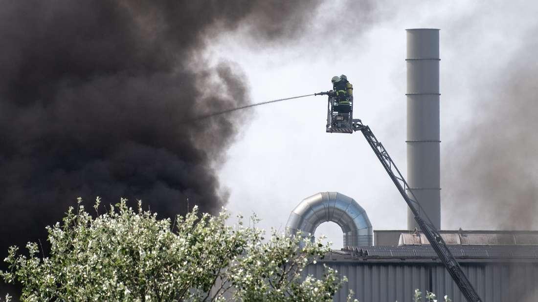 Feuerwehrleute bekämpfen von einer Drehleiter aus einen Brand in einer Lagerhalle.