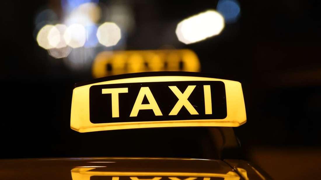 Das Dachschild eines Taxis leuchtet in der Dunkelheit.