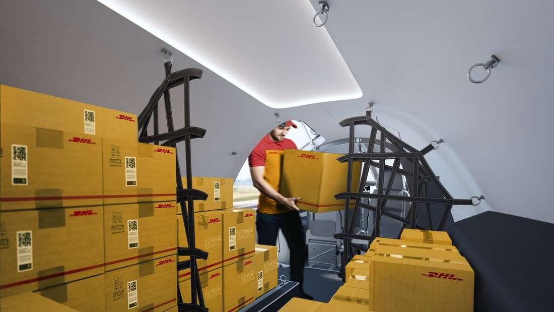 Ein DHL Mitarbeiter packt Pakete in den Frachtraum des E-Flugzeugs.