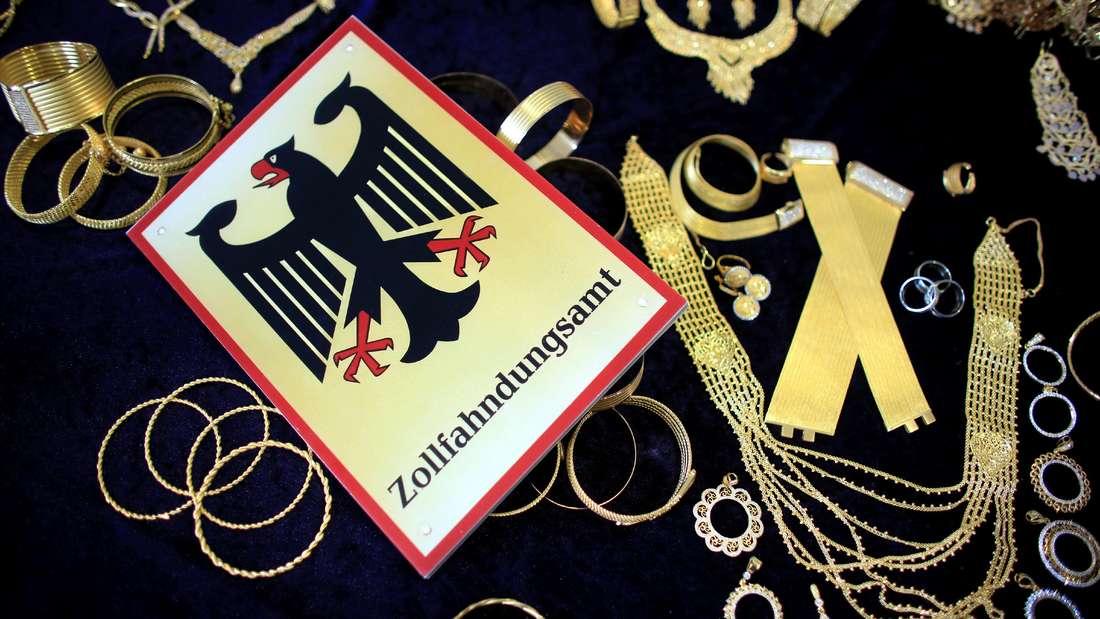 Sichergestellter Goldschmuck liegt auf dem Tisch. Daneben liegt eine Plakette des Zolls.