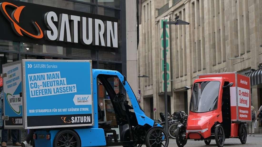 Zwei E-Cargo-Bikes im Look von Saturn und Media Markt stehen vor einer Saturn-Filiale.