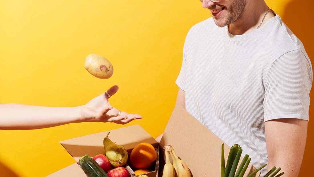 Ein Mann hält ein Paket, gefüllt mit Obst und Gemüse.