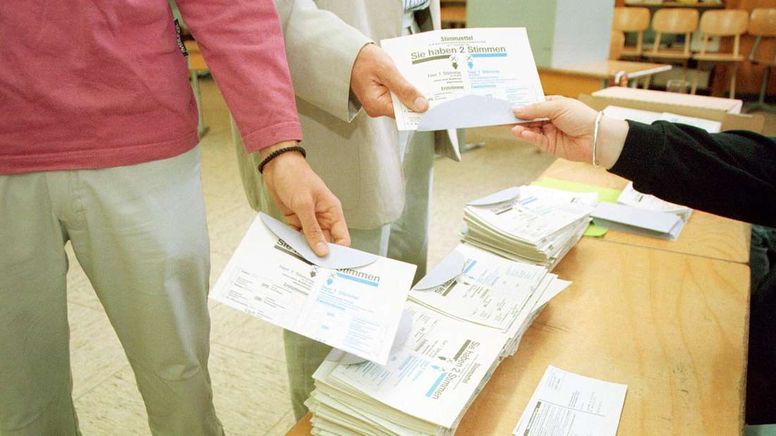 Zwei wahlberechtigte Personen nehmen im Wahllokal ihren Stimmzettel entgegen.