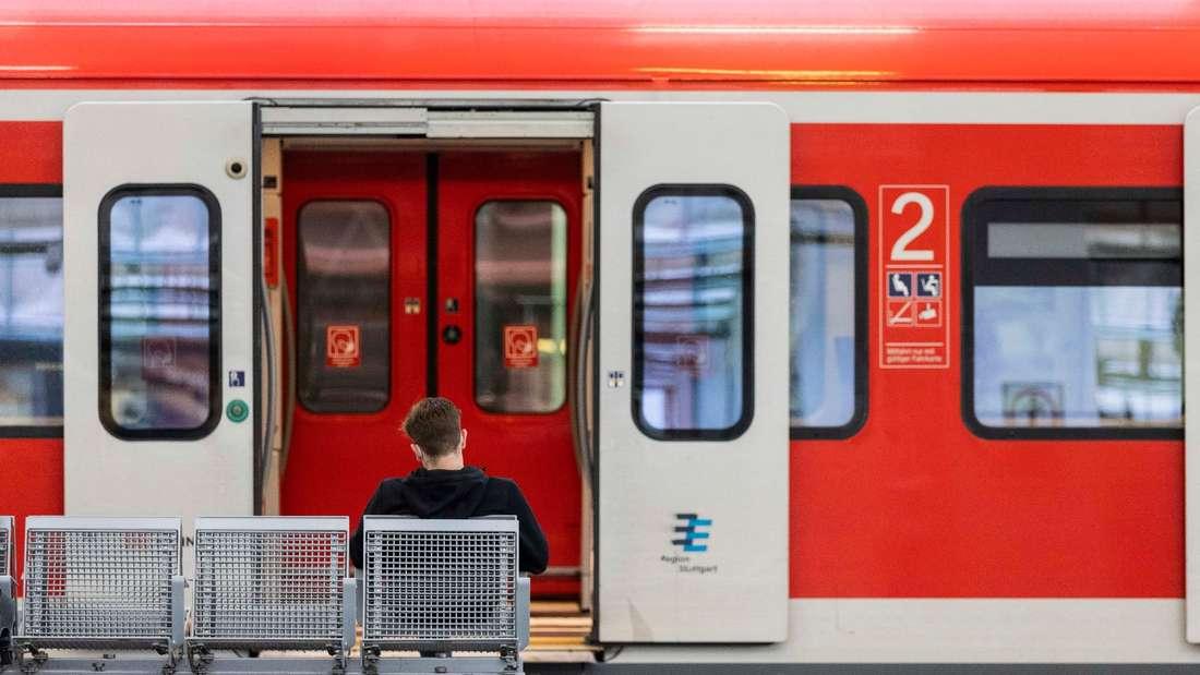 Ein Mann sitzt an einem Bahnhof vor einem Zug