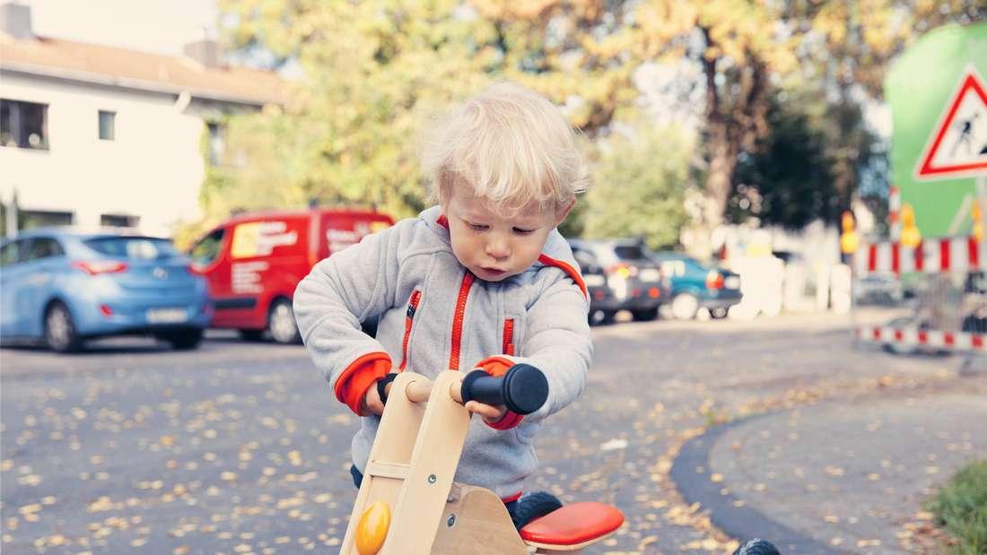 Ein kleines Kind spielt mit einem Dreirad auf der Straße.