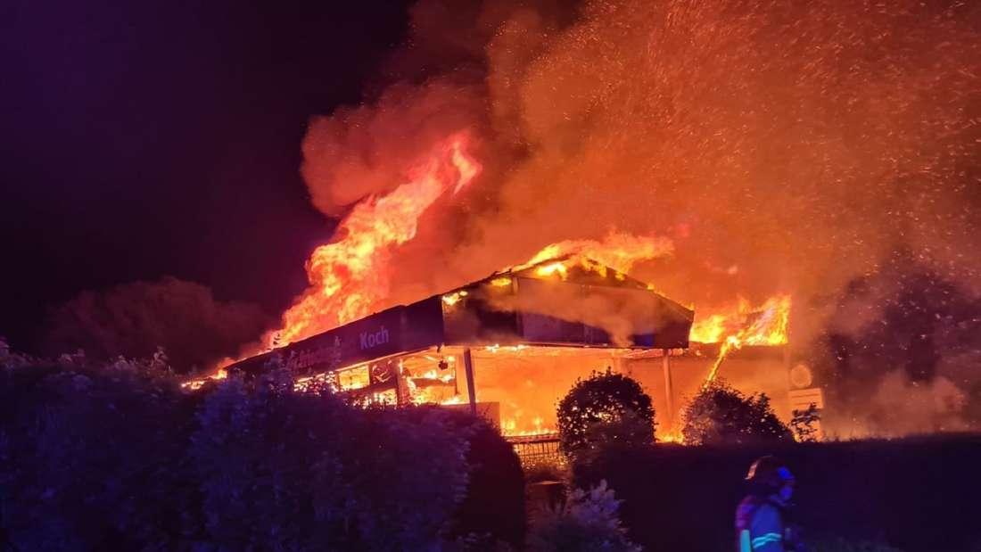 Ein Feuerwehrmann läuft vor einem in Flammen stehenden Supermarkt.