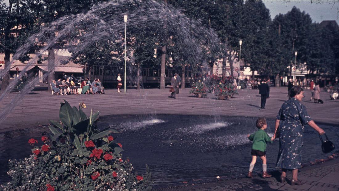Eine Frau geht mit einem Kind an der Hand am Brunnen am Neumarkt in Köln vorbei.