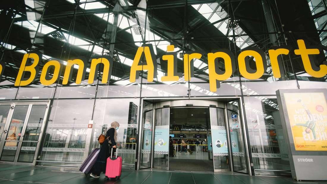Eine Frau geht mit ihren Koffer zum Eingang des Flughafens Köln/Bonn.