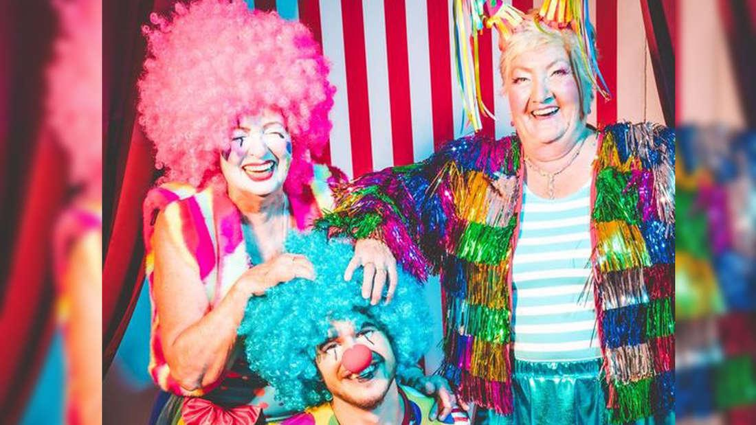 Zwei Clowns und eine Frau mit bunter Lametta-Jacke posieren vor einem bunten Hintergrund.