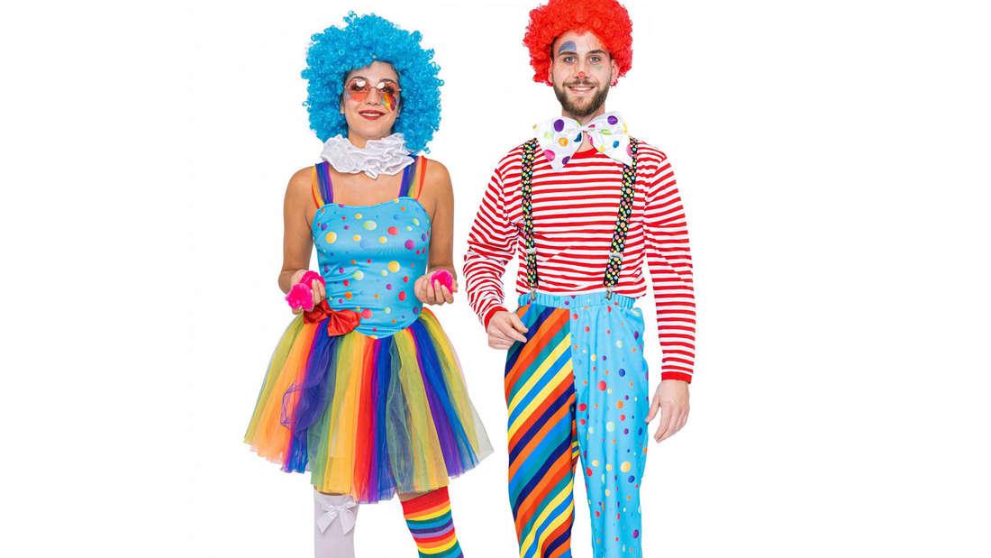 Zwei Jecken in einem bunten Clownskostüm vor einer weißen Wand.