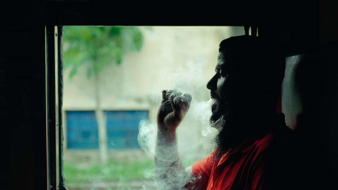 Ein Mann sitzt im Schatten in einem Zug und raucht.