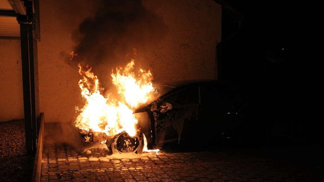 Ein brennendes Auto steht auf einem Parkplatz.