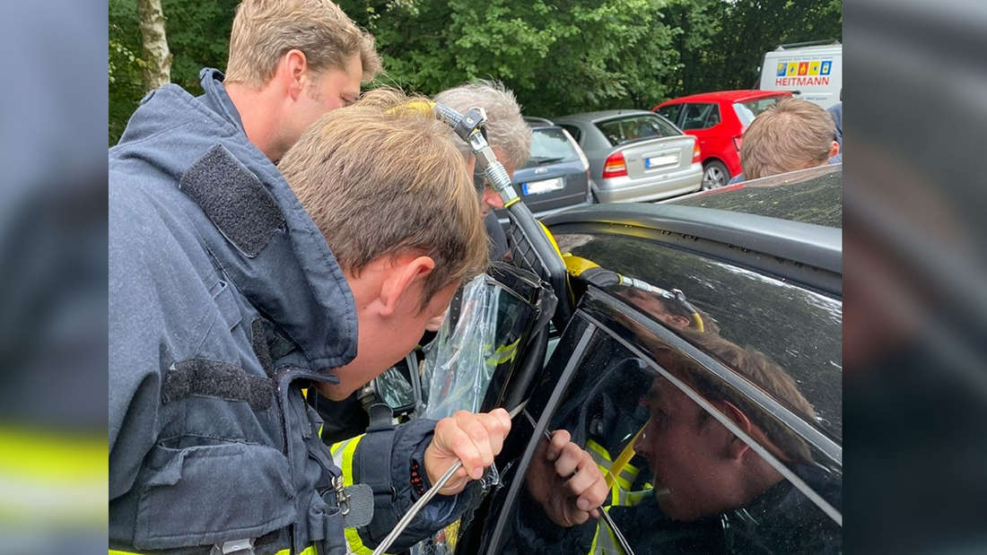 Zwei Feuerwehrmänner befreien einen Einjährigen aus einem verschlossenen Auto.