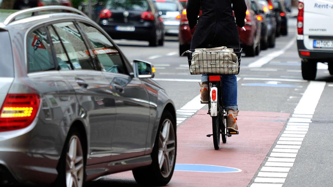 Radfahrerin, im Hintergrund fährt Auto auf Fahrradweg