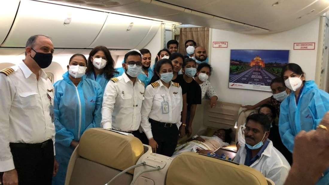 Helfer und Crew stehen in der Business Class eines Air India Dreamliners um eine Mutter, die dort gerade ein Kind geboren hat
