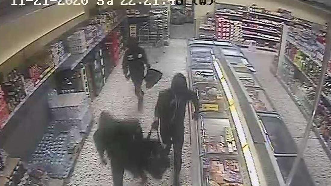 Drei maskierte Männer in einem Supermarkt. Alle drei tragen dunkle Kleidung und eine dunkle Reisetasche.