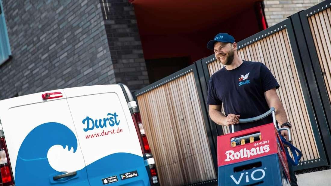 """Ein """"Durst""""-Lieferant bringt Getränke vom Wagen zum Kunden."""