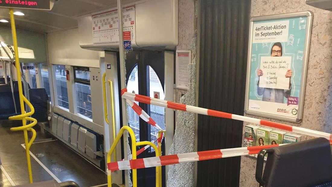 Eine zerstörte Glasscheibe in einer S-Bahn wurde von Absperrband gesichert.